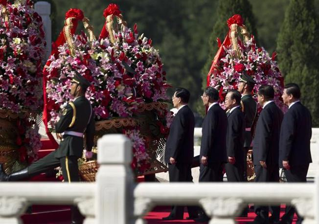 Chinese Paramilitary policemen carry flowers led China's leaders from center to right, President Hu Jintao, Head of Legislature Wu Bangguo, Premier Wen Jiabao, Chairman of Chinese People's Political Consultative Conference Jia Qinglin, and Vice President Xi Jinping as they pay visit to Monument to the People's Heroes during the National Day's ceremony at Tiananmen Square in Beijing Monday, Oct. 1, 2012. (AP Photo/Andy Wong)